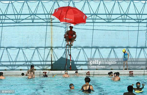 A lifeguard keeps watch in a chair beside a swimming pool on July 7 2008 in Wenzhou of Zhejiang Province China The temperature reached 34 degrees...