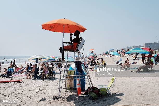 A lifeguard keeps watch over swimmers along Rockaway Beach as visitors try to stay cool on a hot summer day on August 22 2017 in the Queens borough...