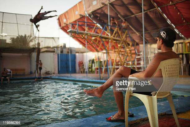 A lifeguard keeps watch over swimmers at a swimming pool July 22 2011 in Baghdad Iraq As the deadline for the departure of the remaining American...
