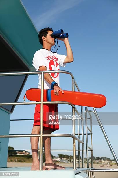 lifeguard looking through binoculars - lifeguard stock pictures, royalty-free photos & images