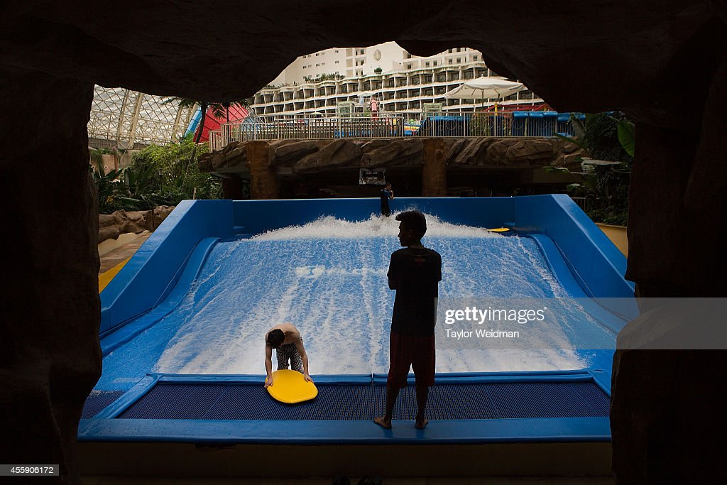 A lifeguard looks on as a young man practices on a surf simulator at the Paradise Island Water Park on September 20, 2014 in Chengdu, China. The Paradise Island Water Park is located inside of the New Century Global Center, the world's largest building measured by floor space, boasting 18,000,000 square feet of floor space.