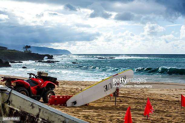 Lifeguard rescue ATV surfboard and jet ski are ready on the beach in case of an emergency during a high surf winter swell on the North Shore of...