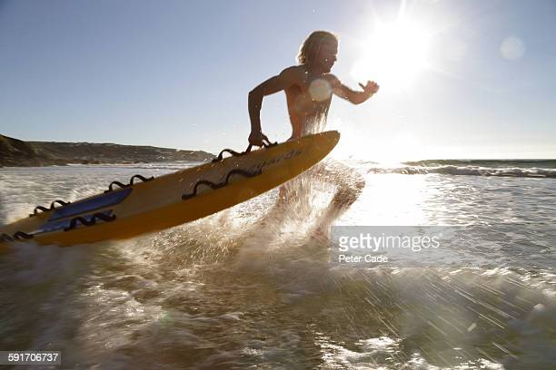 Lifeguard running into sea with rescue board