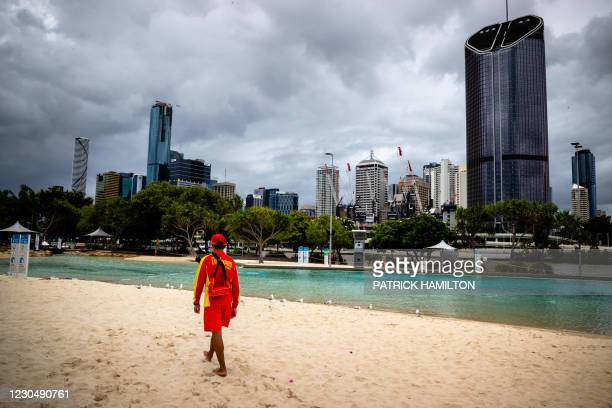 Lifeguard stands watch over a deserted South Bank beach on the first day of a snap lockdown in Brisbane on January 9 with officials elsewhere in...