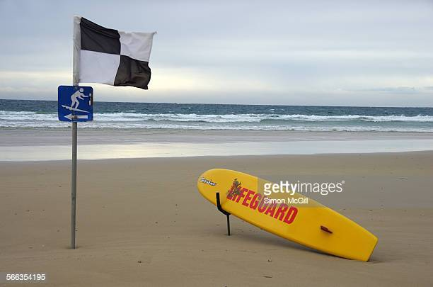 A lifeguard surfboard is propped up ready for an emergency rescue by a pole with black and white quartered flag indicating where surfing is not...