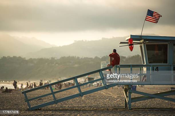 Lifeguard surveys the beach from the railing of his lifeguard station during a summer sunset in Santa Monica, California.