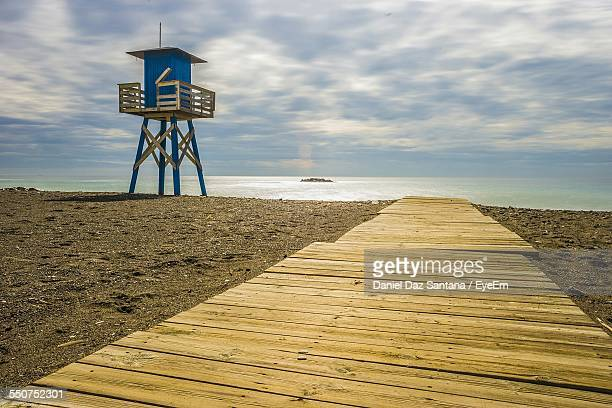Lifeguard Tower And Boardwalk On Beach Against Cloudy Sky