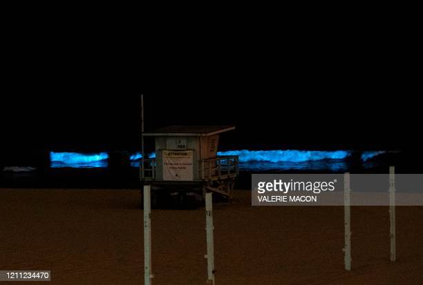 A lifeguard tower is seen as bioluminescent waves crash on the sand shining with a blue glow on April 28 in Manhattan Beach California...