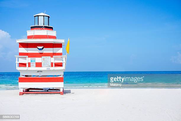 Lifeguard tower on beach with yellow flag