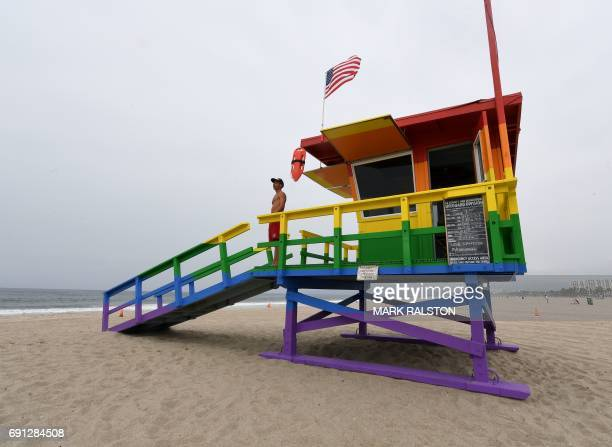 Lifeguard Wadley keeps watch over swimmers at the newly painted Venice Pride Flag Lifeguard Tower after its dedication ceremony at Venice Beach...