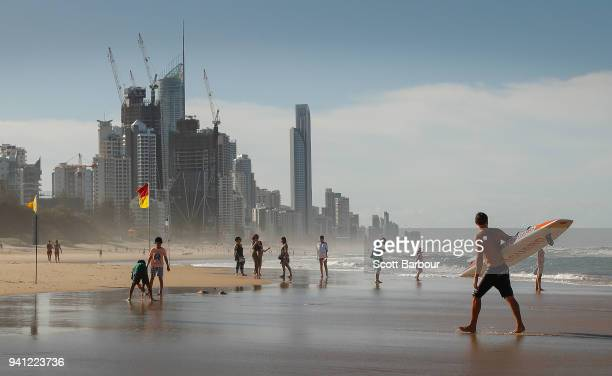 Lifeguard walks along the beach with a surfboard as people swim between the flags ahead of the 2018 Commonwealth Games on April 3 2018 in the Gold...