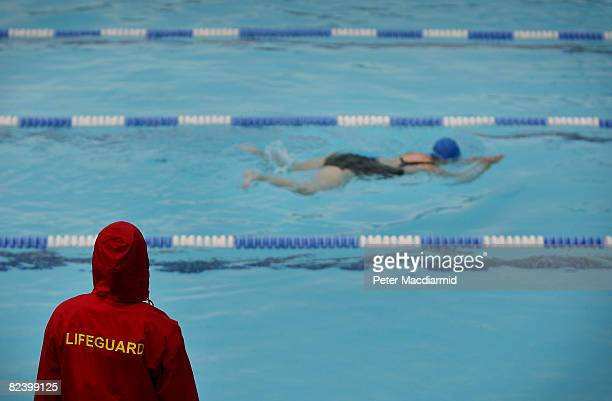A lifeguard watches as a woman swims at Hampton outdoor heated pool on August 18 2008 in London At one time London could boast more that 50 open air...