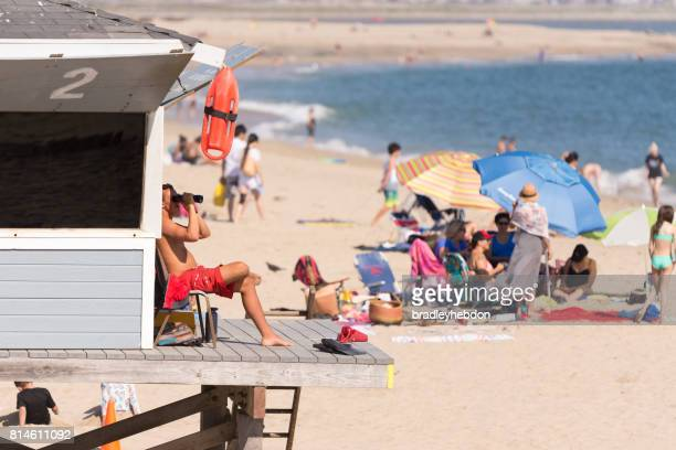 Lifeguard watches from tower in Seal Beach, CA