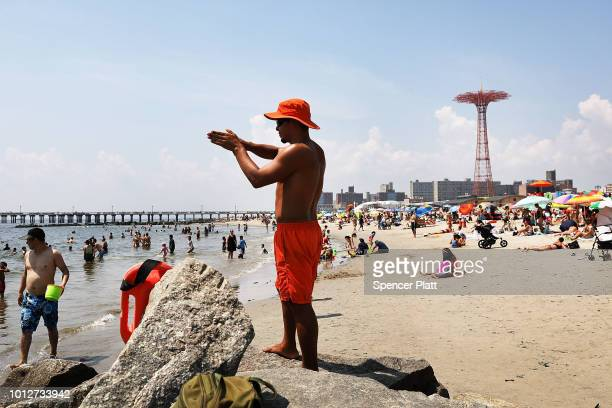 A lifeguard watches swimmers along the beach at Coney Island on a hot summer afternoon on August 7 2018 in the Brooklyn borough of New York City New...