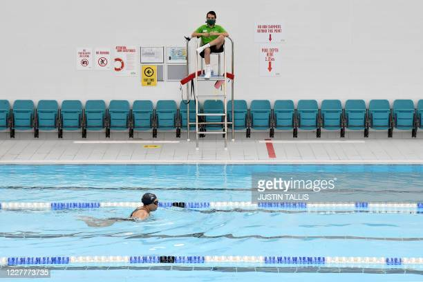 Lifeguard wearing a protective face mask as a precautionary measure against COVID-19 keeps watch over swimmers in the pool at Kensington Leisure...