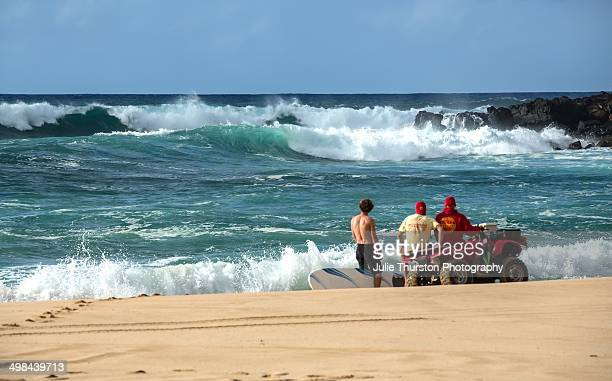 Lifeguards and Surfer With His Surfboard Look at the Ocean Water Conditions at Waimea Beach Park on the North Shore of Oahu Hawaii on a Big Wave...