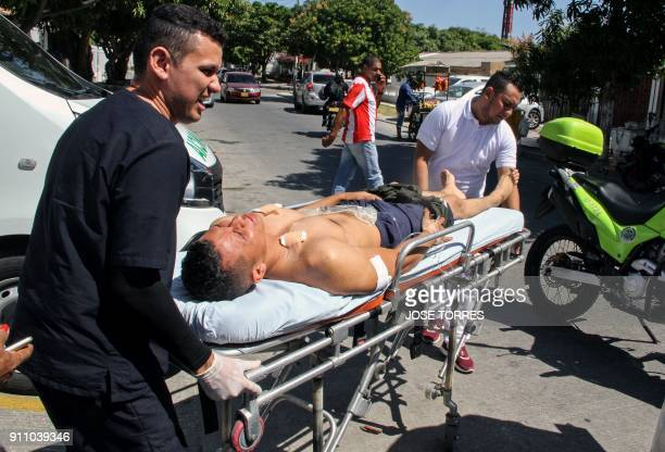 Lifeguards carry a wounded police officer in a bomb attack at a police station in Barranquilla Colombia on January 27 2018 At least three police...