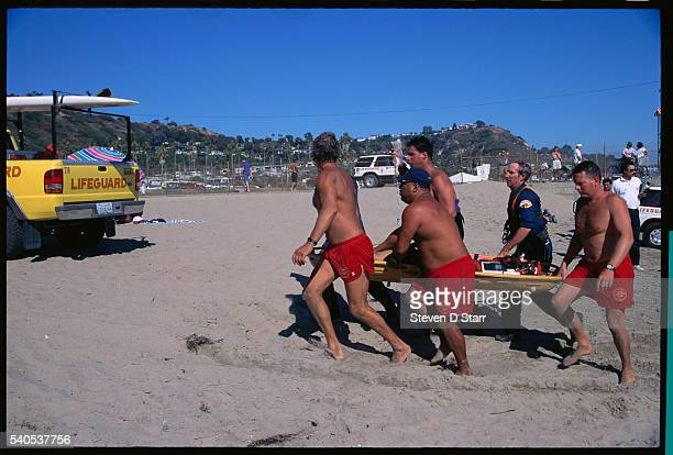Lifeguards carry off the body of a man who drowned near the beach at Santa Monica