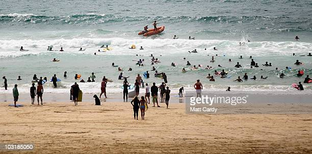 RNLI lifeguards in a inflatable boat patrol as swimmers in the sea enjoy the surf at Booby's near Padstow on July 28 2010 in Cornwall England As more...