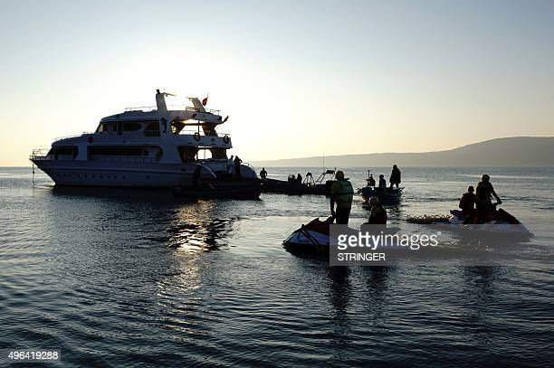 Lifeguards stand with their jet skis next to a yacht that carried refugees and migrants moors near the Greek island of Lesbos on November 9 2015...
