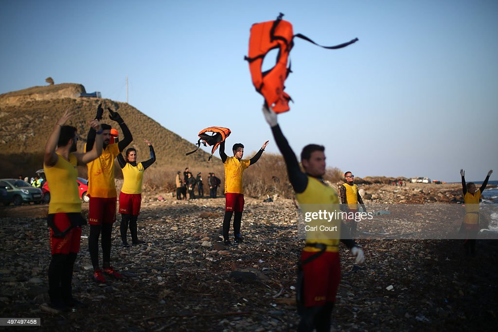 Lifeguards wave lifejackets from the beach as they signal to a migrant boat making the crossing from Turkey to the Greek island of Lesbos on November 17, 2015 in Sikaminias, Greece. Rafts and boats continue to make the journey from Turkey to Lesbos each day as thousands flee conflict in Iraq, Syria, Afghanistan and other countries. Over 500,000 migrants have entered Europe so far this year and approximately four-fifths of those have paid to be smuggled by sea to Greece from Turkey, the main transit route into the EU. Most of those entering Greece on a boat from Turkey are from the war zones of Syria, Iraq and Afghanistan.
