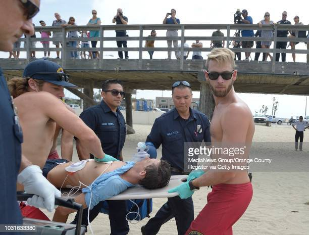 Lifeguards work to rescue Joey Callanan as he plays the part of a drowning victim during a mock rescue near the Seal Beach Pier on Monday The faux...