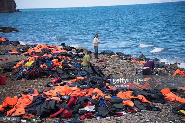 lifejackets from migants scattered on lesbos beaches, greece - lesbos stock photos and pictures