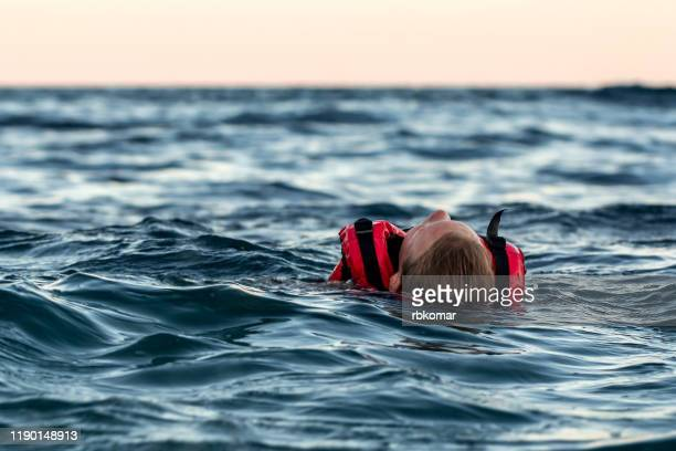 lifeless drowning girl in a life jacket on the high seas at dusk - drowning victim photos stock pictures, royalty-free photos & images