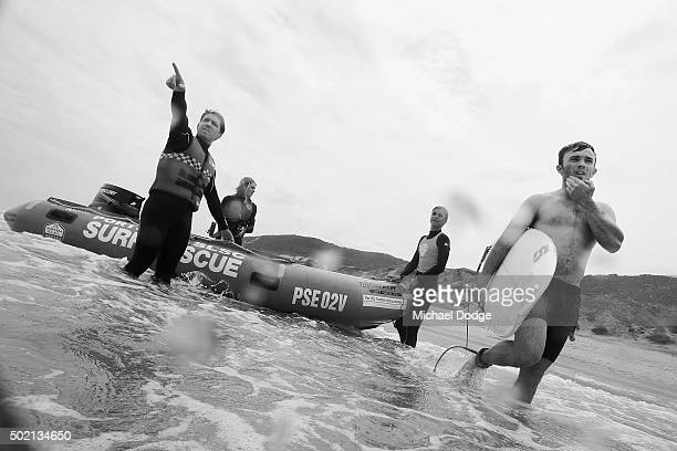 Lifesaver Nicholas Tissot gestures to a surfer where a safer spot to surf is on the Portsea Back Beach on December 6 2015 in Melbourne Australia...
