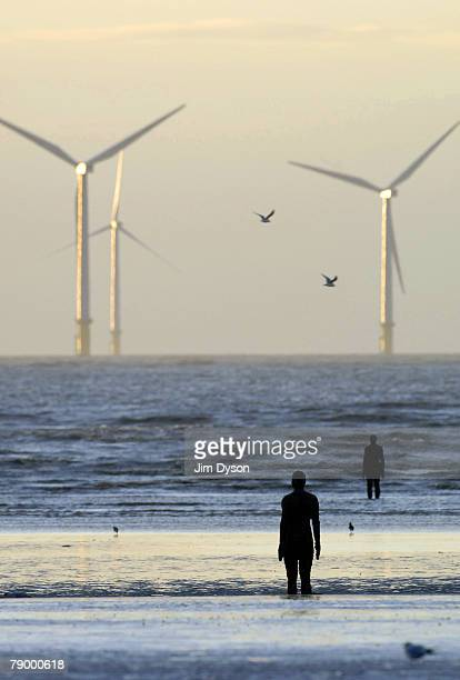 Lifesize body cast statues created by the artist Antony Gormley look out to the Irish Sea to the windmills of Burbo Bank at 'Another Place' on Crosby...