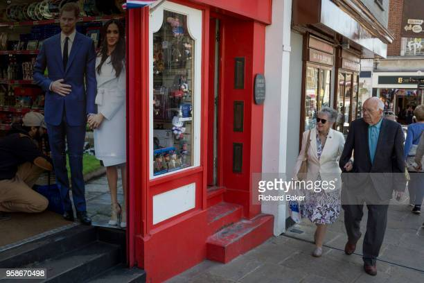 A lifesize standee of Prince Harry and Meghan Markle with souvenirs and merchandise on sale in a the doorway of a tourist trinket window as the royal...