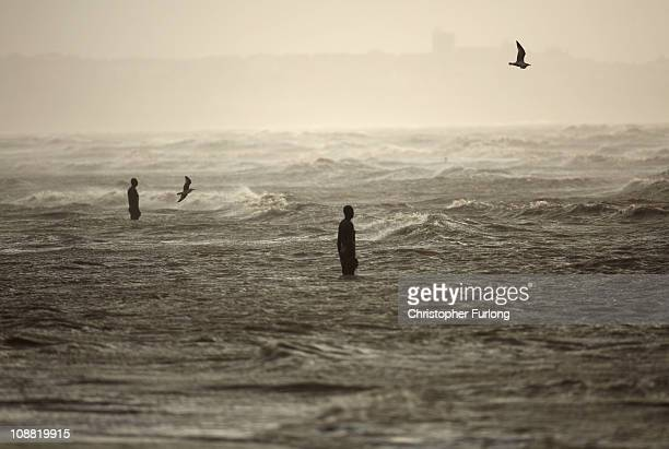Lifesized body cast statues of 'Another Place' created by the artist Antony Gormley is lashed by windswept waves on Crosby Beach as the North of...