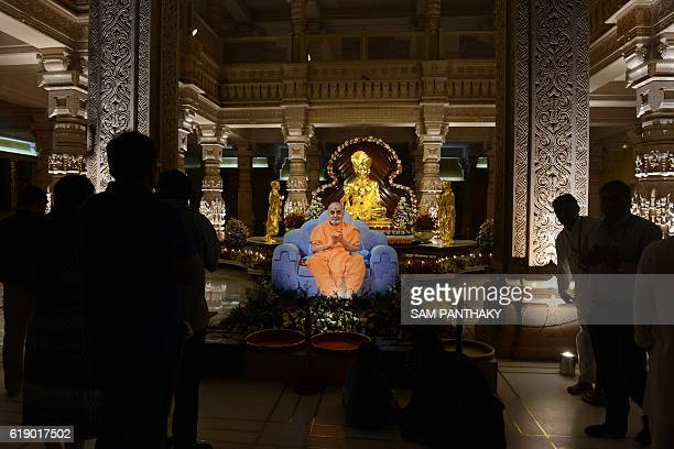 A lifesized photo of Late Pramukh Swami is kept in front of an idol of Lord Swaminarayan at the illuminated Akshardham Temple in Gandhinagar some 30...