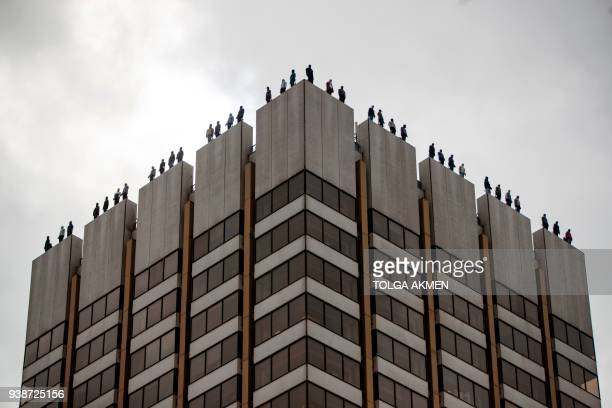 """Life-sized sculptures of 84 men are seen, positioned on the roof of ITV Television Centre building in London on March 27 as part of """"Project 84"""", a..."""