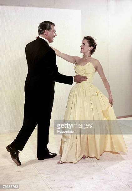 1955 An elegant couple he wearing a dark suit she in evening dress prepare to dance together