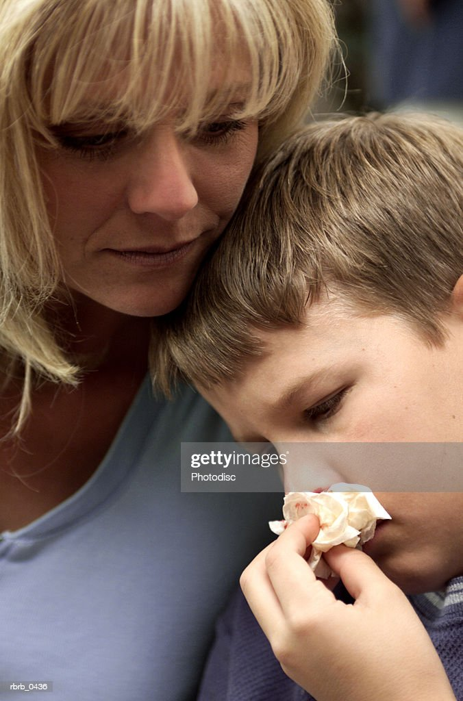 lifestyle photo of a caucasian mother as she consoles her injured son : Stockfoto