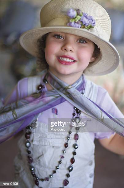 lifestyle photo of a cute little caucasian girl plays dress up in a hat and scarf as she smiles