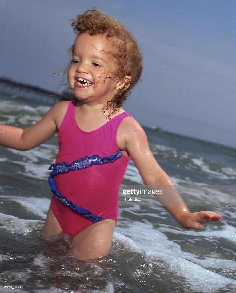 lifestyle photograph of a caucasian female toddler in a swimsuit as she plays in the ocean : Stockfoto
