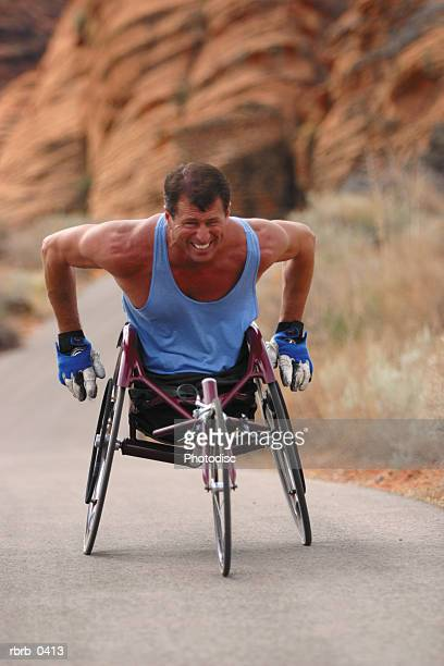 lifestyle photograph of a caucasian male wheelchair racer as he trains in a red rock canyon