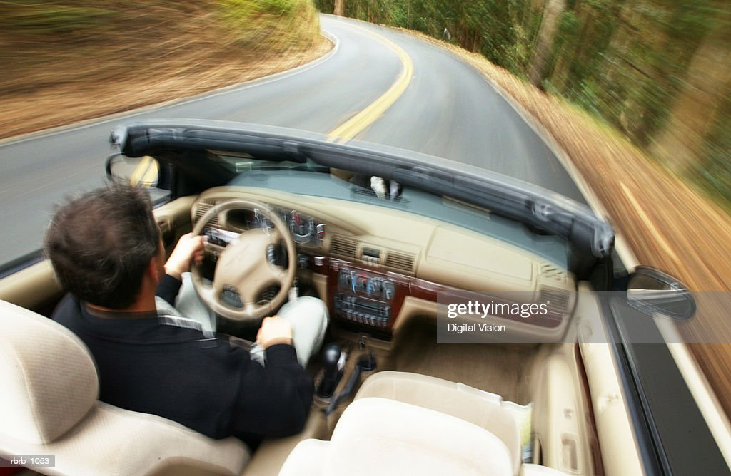 lifestyle photograph of a man speeding down a highway in a convertible : Stockfoto