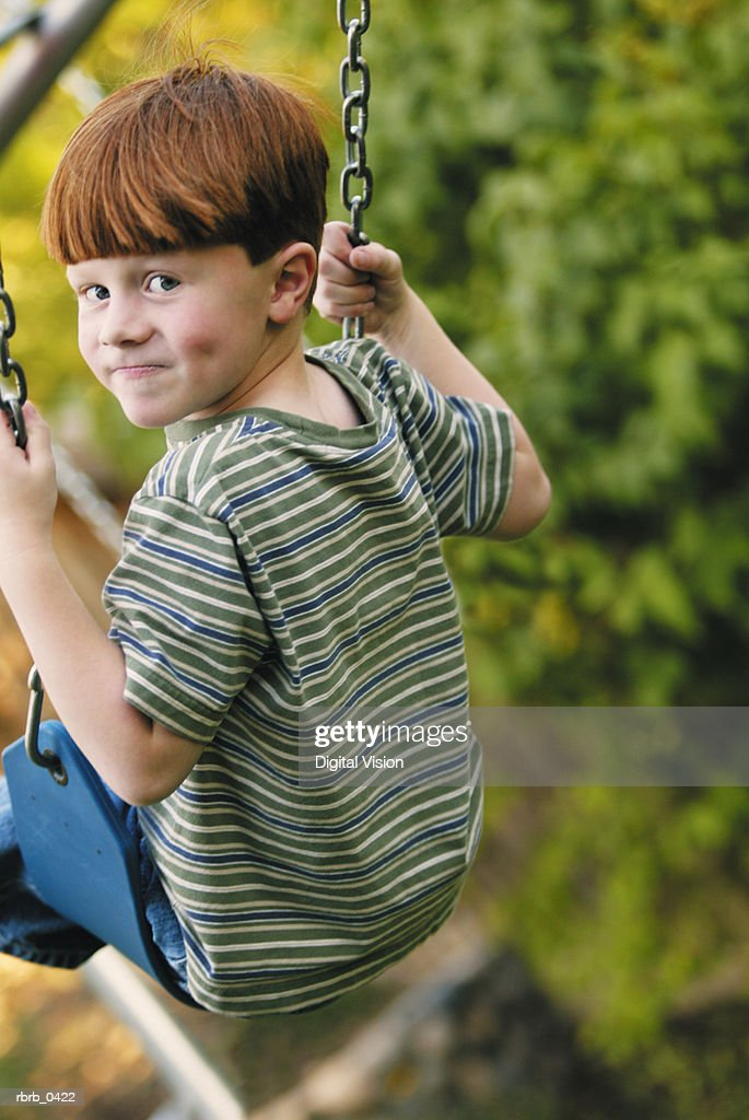 lifestyle photograph of a redheaded caucasian boy as he smiles on a swing : Stockfoto