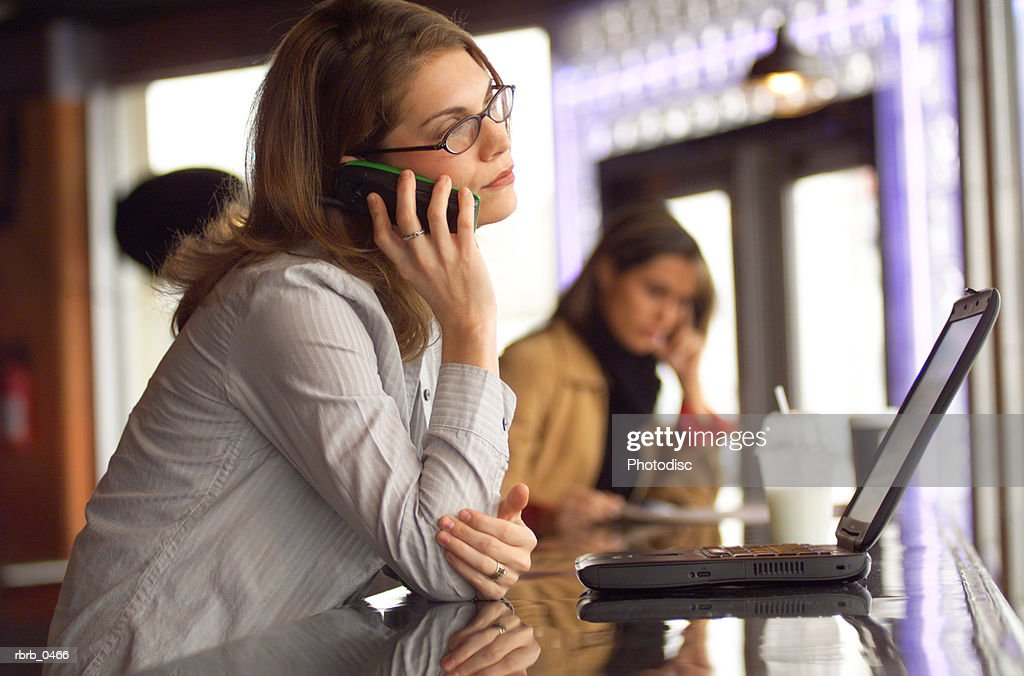 lifestyle photograph of an attractive caucasian female as she talks on a cell phone in a cafe : Stockfoto