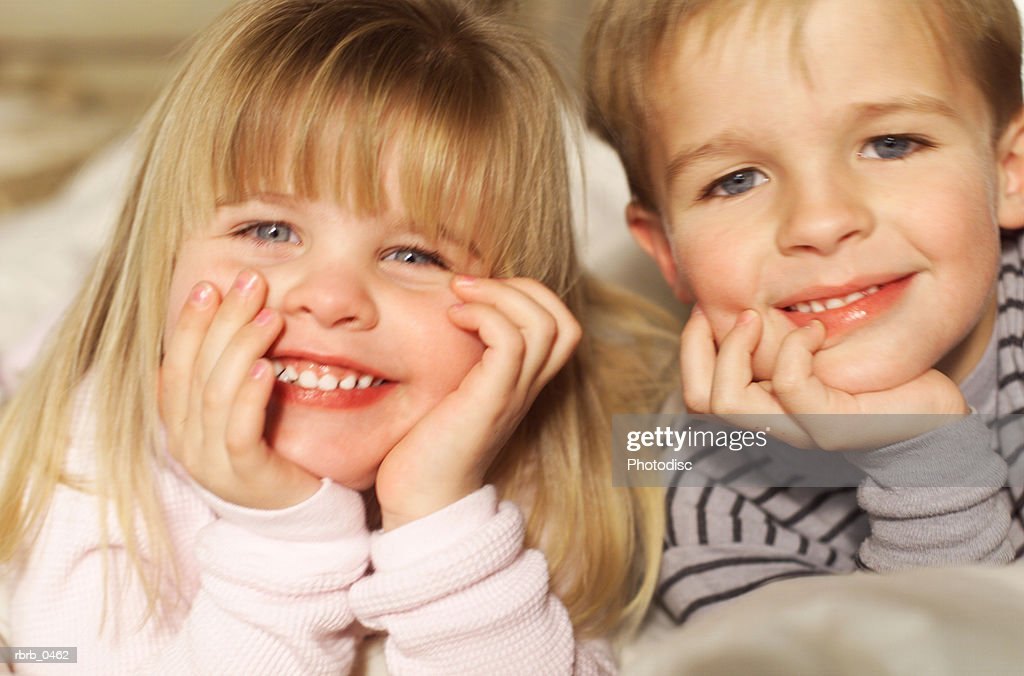 lifestyle photograph of two young caucasian siblings as they smile at the camera : Stockfoto