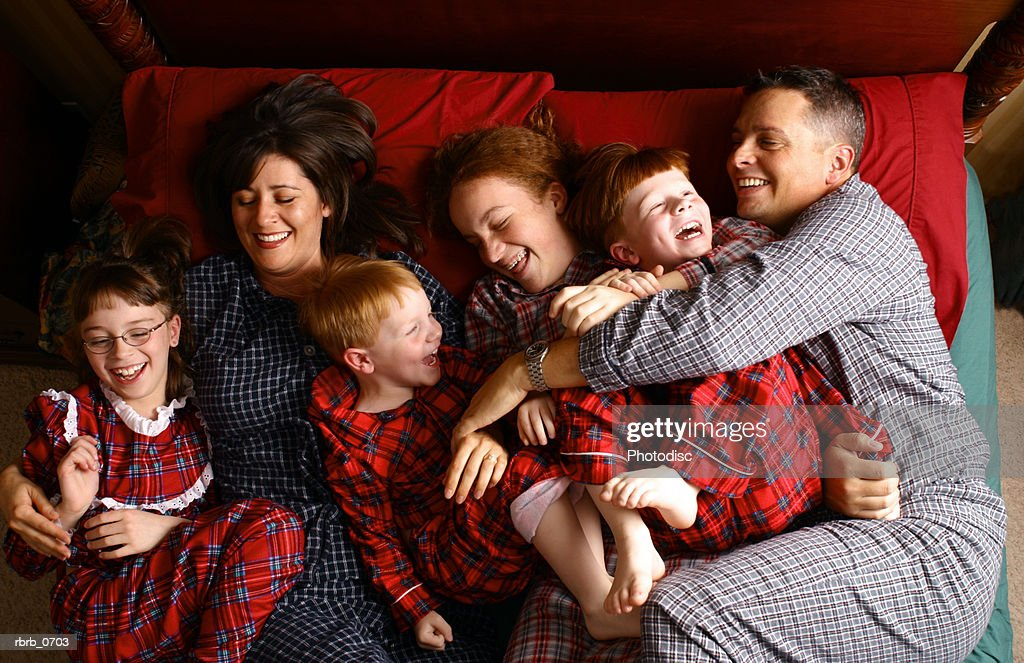 lifestyle portrait of a caucasian family in their pajamas lying in bed : Stockfoto