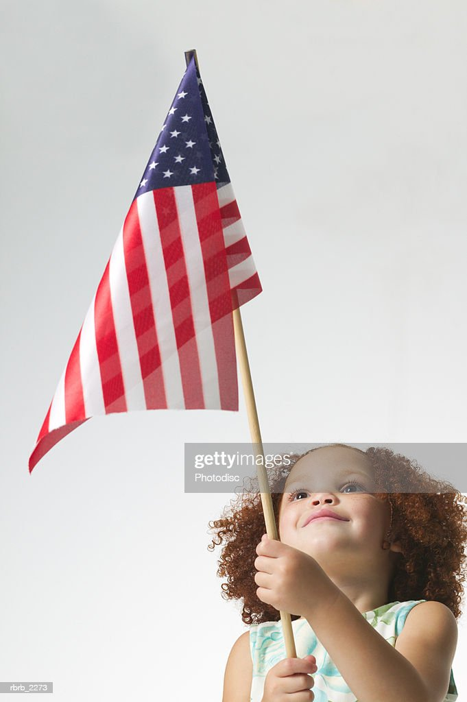 lifestyle portrait of a female child as she looks up at an american flag : Foto de stock