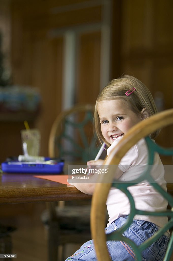 lifestyle portrait of a female child drawing at a table as she turns and smiles : Stockfoto