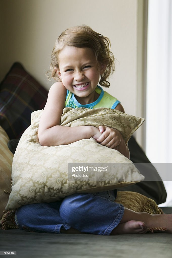 lifestyle portrait of a female child in a green shirt as she sits on a couch and hugs a pillow : Stockfoto