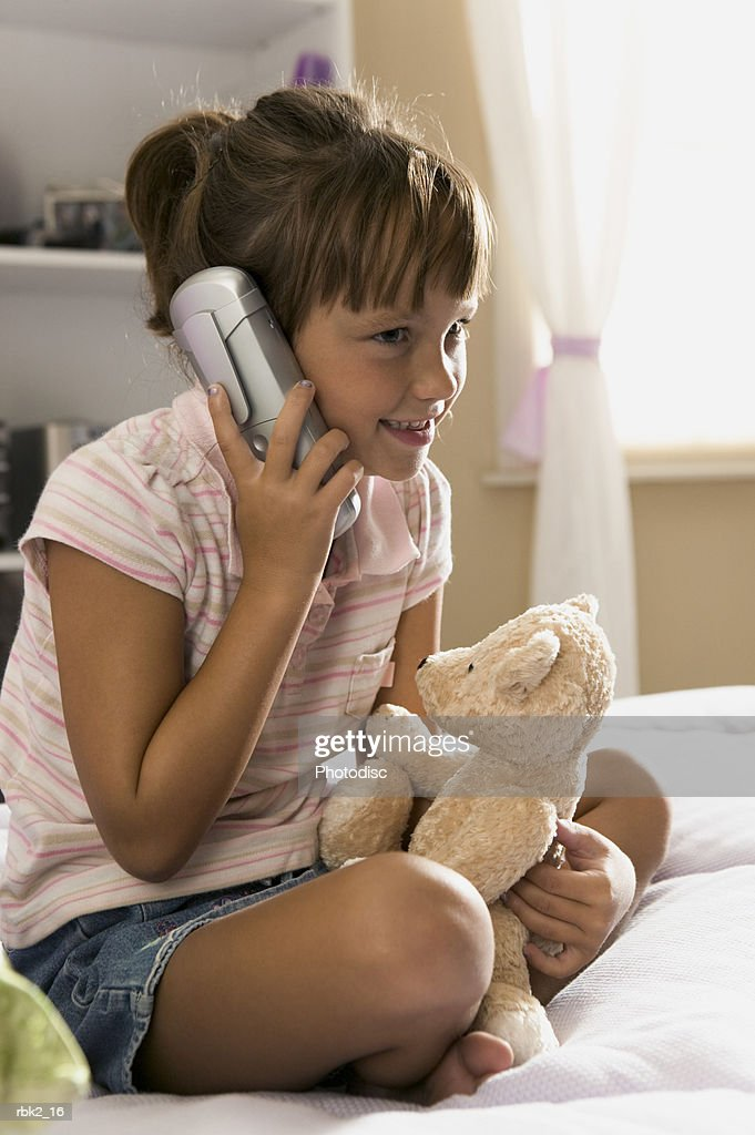 lifestyle portrait of a female child in a pink striped shirt as she chats on the phone : Stockfoto