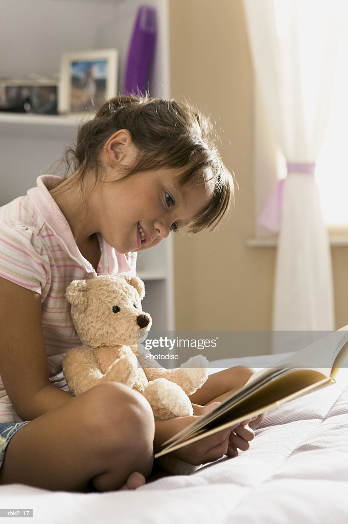 lifestyle portrait of a female child in a pink striped shirt as she sits in her bedroom and read a book : Stockfoto