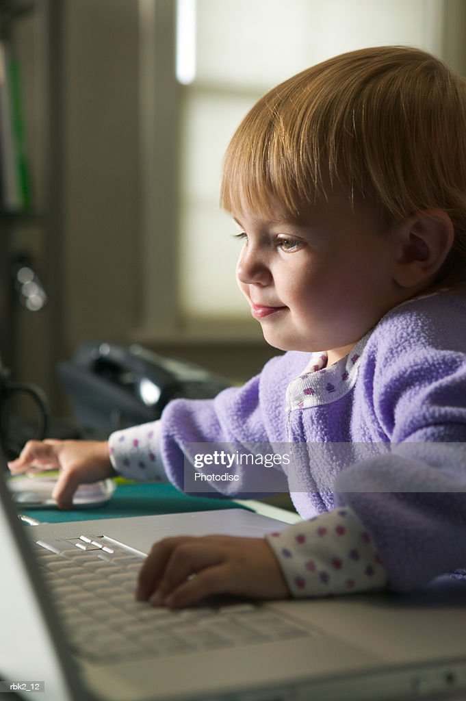 lifestyle portrait of a female toddler in purple pajamas as she plays on a computer : Stockfoto